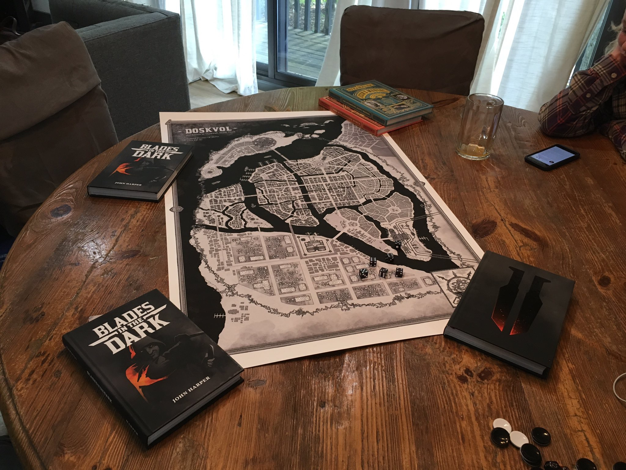 Photo of a gaming table with a large map of Duskvol and several copies of Blades in the Dark.